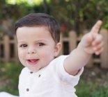 Portrait de sourire de petit garçon, pointant son doigt — Photo de stock