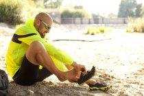 Человек в спортивной одежде сидит на земле и обувается. — стоковое фото