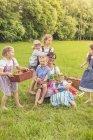 Kinder mit Lehrer in traditionellen Kostümen auf Wiese — Stockfoto