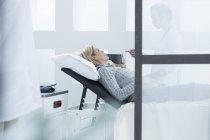 Женщина лежит на кровати во время осмотра в больнице — стоковое фото