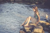 Girl sitting at waterside checking temperature of the water — Stock Photo
