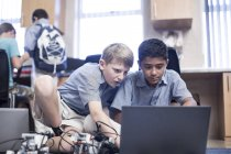 Schoolboys using laptops in robotics class — Stock Photo