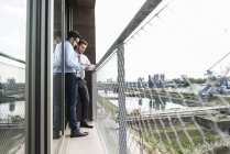 Dos jóvenes empresarios discutiendo documentos en el balcón - foto de stock