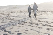 Madre y su hijo caminando por la playa en la hermosa naturaleza - foto de stock