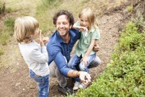Father with two children collecting blueberries in the nature — Stock Photo