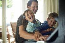 Батько грати на фортепіано з дочкою на колінах і сина — стокове фото