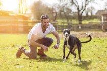 Портрет человека, играющего со своей собакой на лугу — стоковое фото