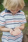Little boy looking at caterpillar of peacock butterfly in hands — Stock Photo