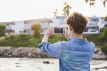 Greece, Rhodes, young man photographing with smartphone at seafront — Stock Photo