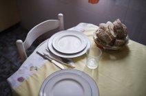 Tavolo preparato per due persone con cesto di pane — Foto stock