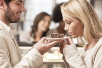 Man holding plate with pastry, woman smelling flavor — Stock Photo