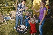 Happy family having a barbecue in garden — Stock Photo