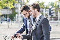 Dos jóvenes hombres de negocios caminando por la ciudad, mirando el teléfono móvil - foto de stock
