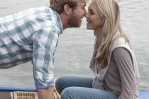 Young couple face to face in a canoe on a lake — Stock Photo