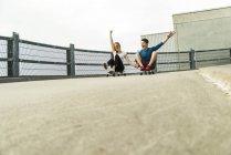 Enthousiaste jeune couple équitation descente avec planches à roulettes — Photo de stock