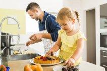 Père et fille dans la cuisine à préparer des gâteaux aux fruits — Photo de stock