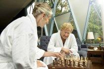 Senior couple in bathrobes playing chess — Stock Photo