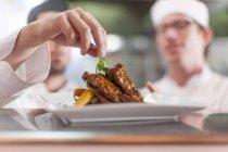 Chef guarnición placa con el alimento, closeup - foto de stock