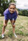 Портрет девушки, стоящей на лугу и смотрящей на зрителя — стоковое фото