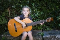 Niña tocando guitarra española en el exterior - foto de stock