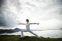 Austria.Kranzhorn, Mid adult woman practising yoga on mountain top — Stock Photo