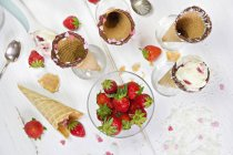 Glass with strawberries, ice-cream cones and topping — Stock Photo