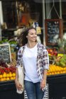 Smiling young woman at greengrocer's shop — Stock Photo