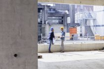 Two men with hard hats talking on construction site — Stock Photo