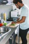 Hombre joven de verduras corte en su cocina - foto de stock