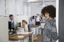 Smiling woman in office with colleagues in background — Stock Photo