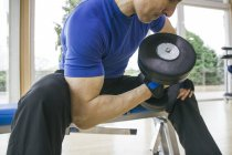Man lifting a dumbbell sitting on a bench in a gym — Stock Photo