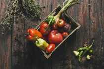 Fresh vegetables in crate on dark wooden surface with herb — Stock Photo