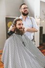 Barber cutting beard of a customer and looking in mirror — Stock Photo