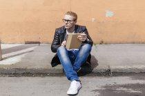 Молода людина з цифровий планшет, сидів на узбіччі — стокове фото