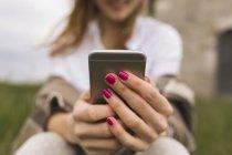 Mãos de mulher segurando smartphone — Fotografia de Stock
