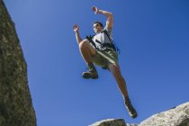 Spain, hiker with backpack jumping on the rocks in La Pedriza — Stock Photo