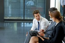 Three business colleagues with digital tablet discussing in office lobby — Stock Photo