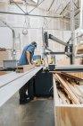 Плотник, работающий с пилой — стоковое фото
