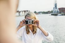 Germany, Luebeck, woman taking picture at the waterside — Stock Photo