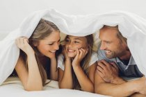Happy father, mother and daughter under blanket — Stock Photo