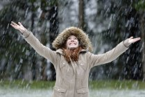 Girl enjoying snow fall, beginning of winter — Stock Photo