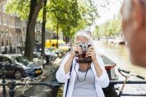 Paesi Bassi, Amsterdam, donna anziana che scatta una foto con fotocamera analogica al canale cittadino — Foto stock