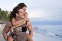Young man giving his girlfriend a piggyback ride on the beach — Stock Photo