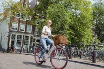 Netherlands, Amsterdam, woman riding bicycle  in the city — Stock Photo