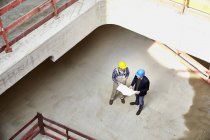 Construction worker and architect with plan talking on construction site — Stock Photo