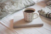 Buch und eine Tasse schwarzen Kaffee auf einem Bett — Stockfoto