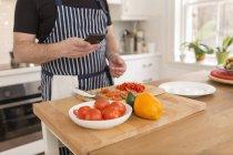 Uomo che utilizza smartphone durante la preparazione del cibo in cucina, vista parziale — Foto stock