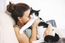 Женщина, сидящая на диване и обнимающая своего кота — стоковое фото