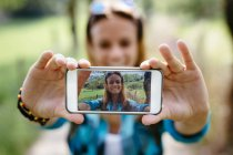 Smiling teenage girl taking a selfie with smartphone — Stock Photo