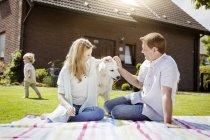 Família feliz com cão relaxante no jardim — Fotografia de Stock